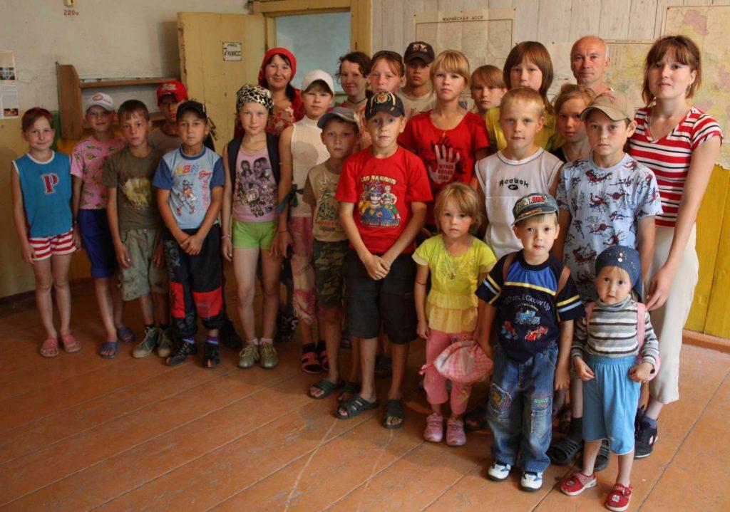 А. Ф. Петрушин (в третьем ряду второй справа) с детьми и их родителями из соседнего села Большой Рой, приехавшими в музей деревни Тюм-Тюм на экскурсию. Август 2009 г.